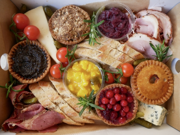 pork pies with cheese, pickles, baguette, tomatoes presented in a takeaway box